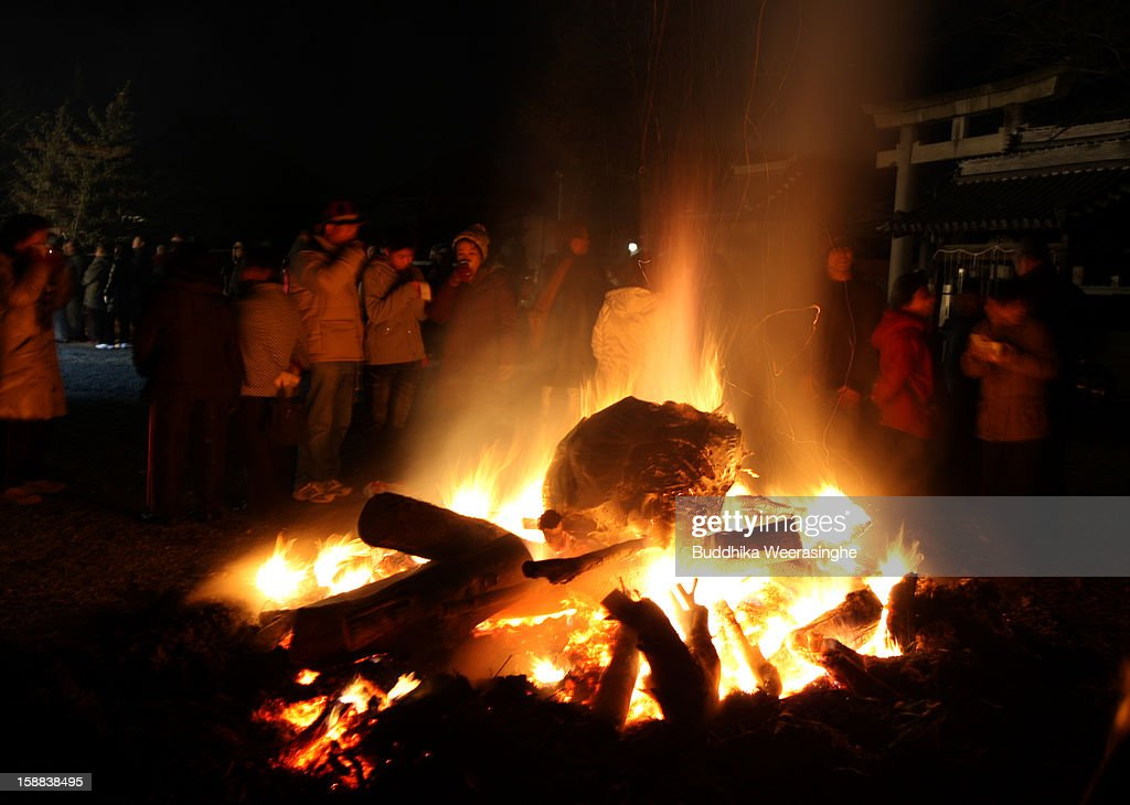 Japanese people stand close to a fire to warm up during the New Year blessing at the Sagami-ji Buddhist temple on January 1, 2013 in Kasai, Japan. Japanese people attend the Buddhist temple at midnight on December 31 for the ringing of the temple bell to welcome in the New Year or 'Omisoka' as it is known in Japan. In Japanese belief there are 108 elements to the human mind, so the bell is rung 108 times as a blessing of happiness for the New Year.