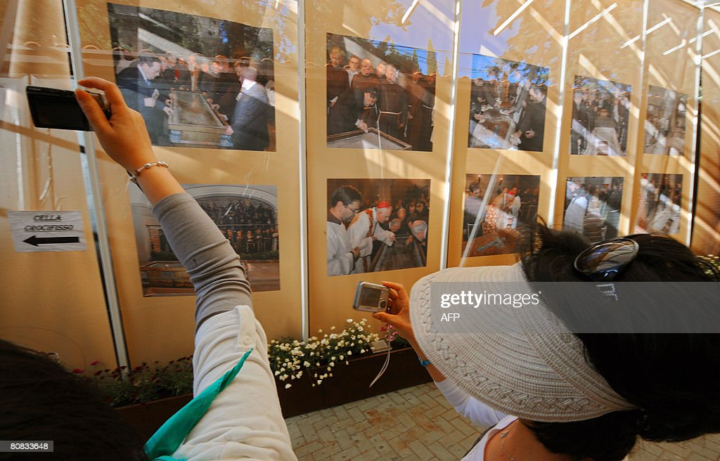 Japanese pilgrims take pictures at an exhibition about padre Pio's exhumation in the old Church of St Mary of Grace at San Giovanni Rotondo in the...