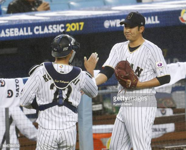 Japanese pitcher Tomoyuki Sugano and catcher Seiji Kobayashi pat hands after the second inning in a World Baseball Classic semifinal game against the...