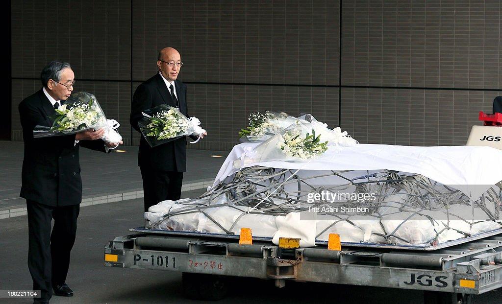 Japanese plant construction company JGC Co president Koichi Kawana (R) offers a flower bunch on the coffin of their supreme advisor Tadanori Aratani, who was killed in Algerian hostage crisis, at Narita International Airport on January 26, 2013 in Narita, Chiba, Japan.