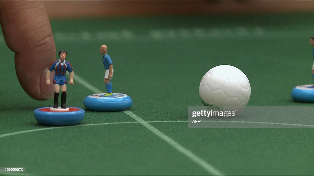 A Japanese player flicks a two-centimetre plastic player to move the ball during a Subbuteo table football tournament in Yokohama on April 14, 2013. 14 players from the world played on the small fields and Frenchman Cedric Garnier (unseen in this picture) won the annual Yokohama tournament. Fans of Subbuteo from around the world have brought their low-tech table-top sport to high-tech Japan, in the hope of persuading a nation of video gamers to get offline. PHOTO / Antoine BOUTHIER