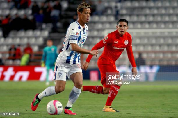 Japanese player Keisuke Honda of Pachuca runs with the ball pressured by Efrain Velarde of Toluca during the Mexican Apertura tournament football...