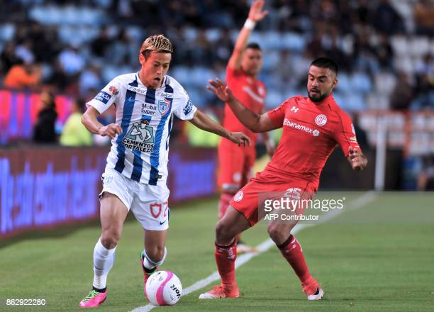 Japanese player Keisuke Honda of Pachuca vies for the ball with Pedro Canelo of Toluca during the Mexican Apertura tournament football match at the...