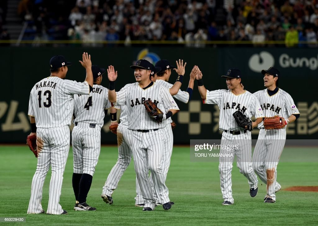 Japanese players celebrate their victory over Cuba after the top of the ninth inning during the World Baseball Classic Pool E second round match between Cuba and Japan at Tokyo Dome in Tokyo on March 14, 2017. /