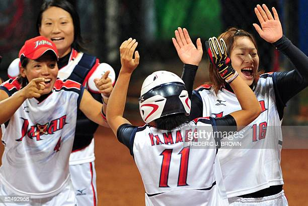 Japanese players celebrate with Eri Yamada after her fourth inning homerun off a pitch by Cat Osterman of the US in their gold medal final at the...