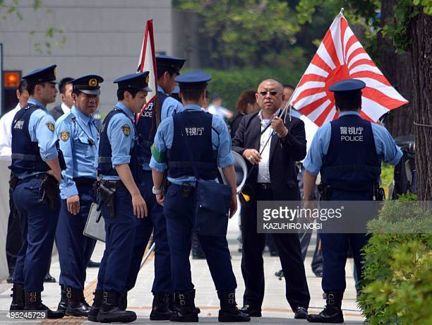 Japanese police confront a man holding a 'Rising Sun' flag near where former 'comfort women' and their supporters are staging a demonstration near...