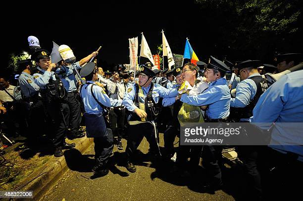 Japanese police officers detain a protester during a rally against the security bills in front of the National Diet building in Tokyo Japan on...