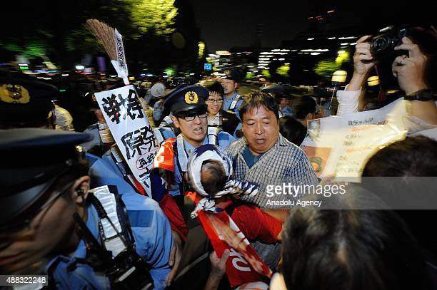 Japanese police officers intervene protesters during a rally against the security bills in front of the National Diet building in Tokyo Japan on...