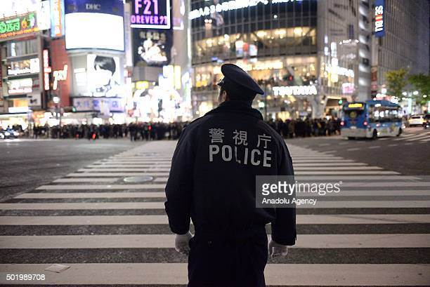 Japanese police officers stand guard as River Plate fans gather to show their support in Tokyo Shibuya Ward Japan on December 19 ahead of the FIFA...