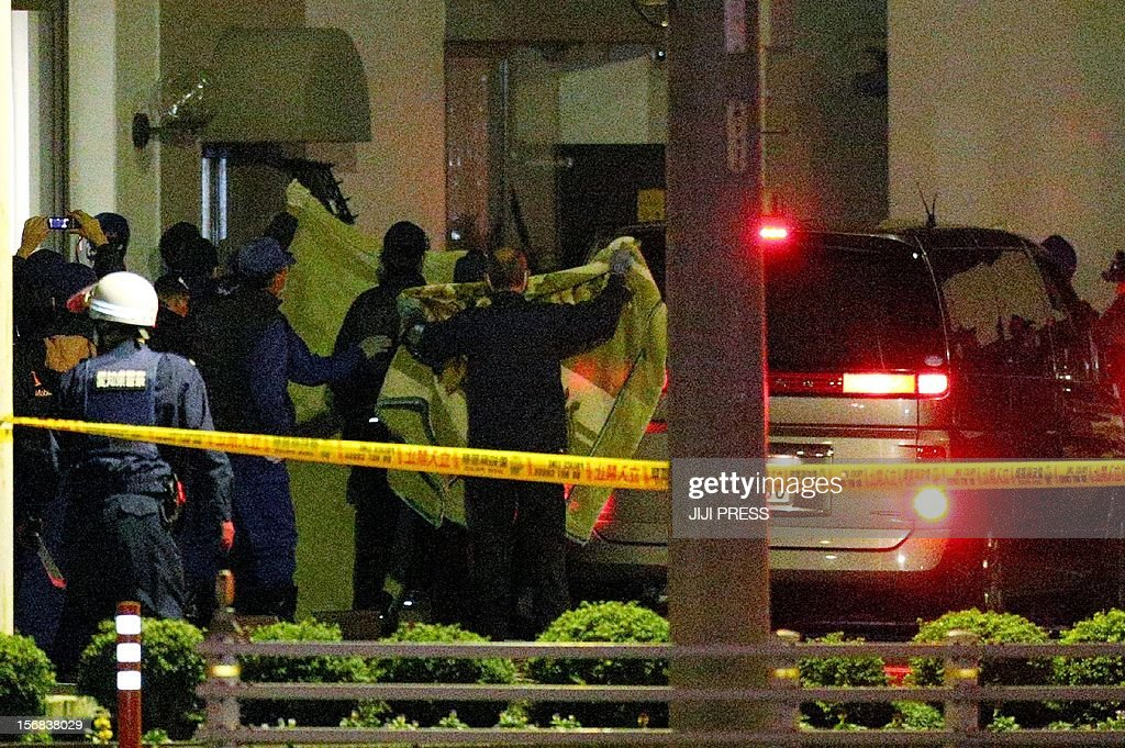 Japanese police rescue hostages behind a curtain (L) as they raid the Zoshi branch of the Toyokawa Shinkin Bank at Toyokawa City in Aichi prefecture, central Japan on November 23, 2012 after a 32-year-old man began a siege on November 22. Japanese police rescued four hostages from a bank on November 23 and arrested the knife-wielding man who had held them captive for more than 12 hours while demanding the prime minister resign, officials said. AFP PHOTO / JIJI PRESS JAPAN OUT