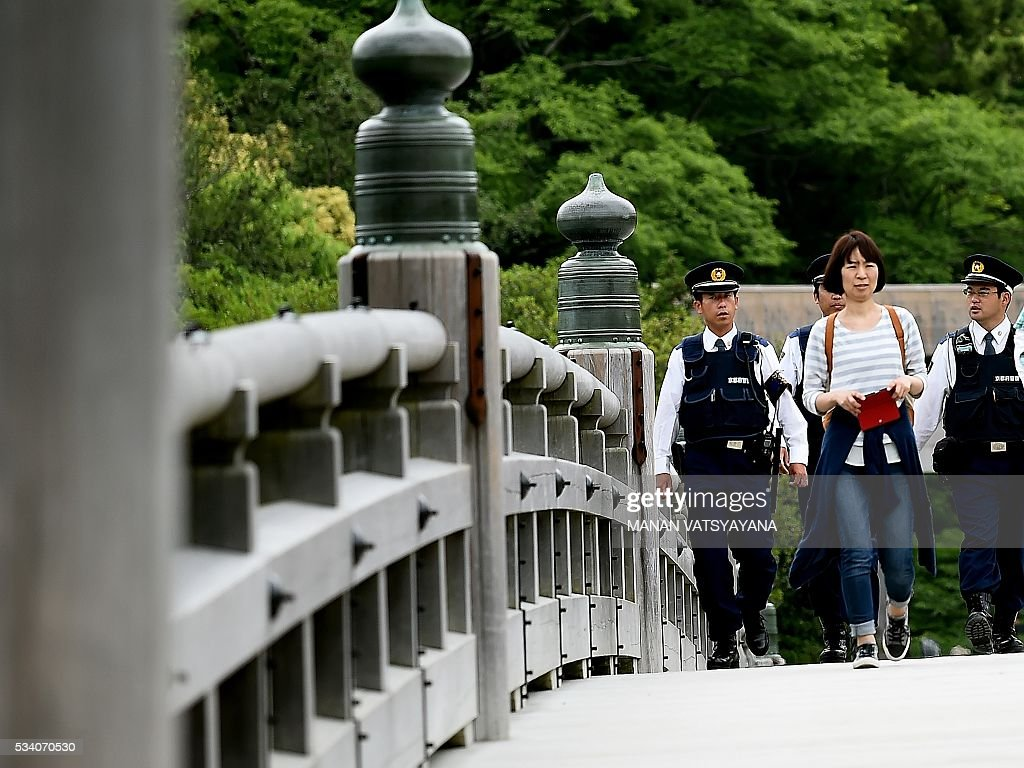 Japanese police walk over the Ujibashi Bridge, leading to the Inner Shrine of the Ise Grand Shrine in Ise-Shima, 300 kilometres southwest of Tokyo on May 25, 2016, ahead of the 2016 Ise-Shima G7 Summit. The annual event, which takes place on May 26-27, draws leaders from some of the world's richest nations, including US President Barack Obama and German Chancellor Angela Merkel. VATSYAYANA