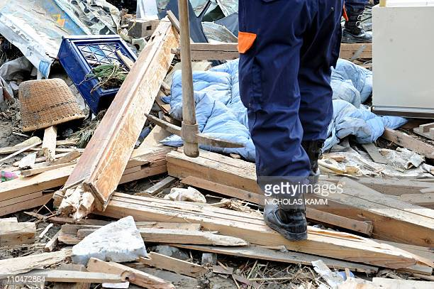A Japanese policeman from Tokyo carries a pickax as he walks through rubble in the devastated town of Rikuzentakata in Iwate prefecture on March 19...