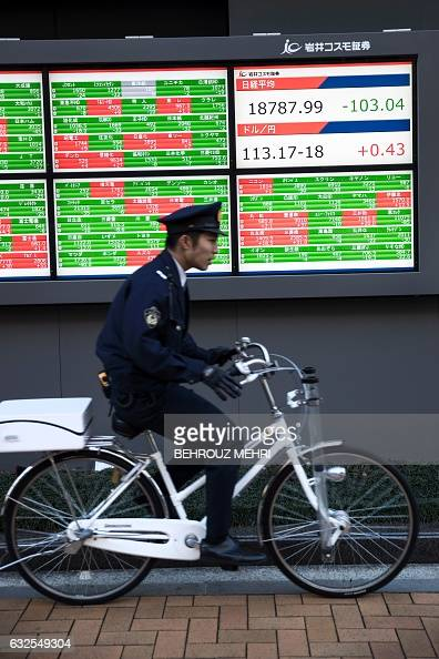 A Japanese policeman rides his bicycle past an electric quotation board flashing numbers of the Nikkei key index of the Tokyo Stock Exchange and the...