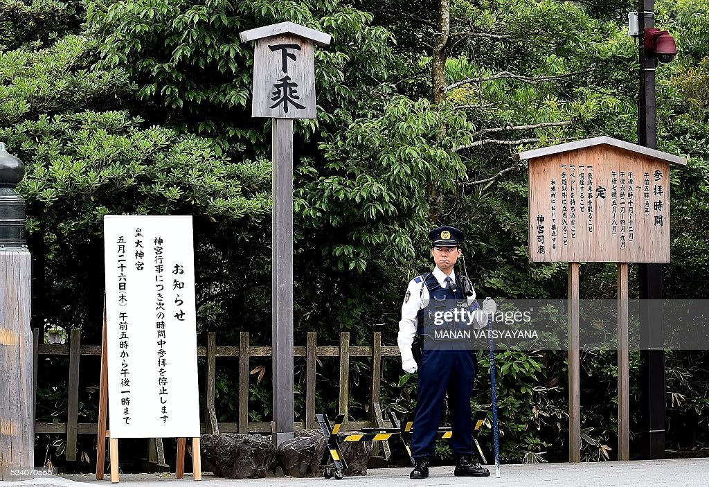 A Japanese policeman stands guard near a traditional gate over the Ujibashi Bridge, leading to the Inner Shrine of the Ise Grand Shrine in Ise-Shima, 300 kilometres southwest of Tokyo on May 25, 2016, ahead of the 2016 Ise-Shima G7 Summit. The annual event, which takes place on May 26-27, draws leaders from some of the world's richest nations, including US President Barack Obama and German Chancellor Angela Merkel. VATSYAYANA