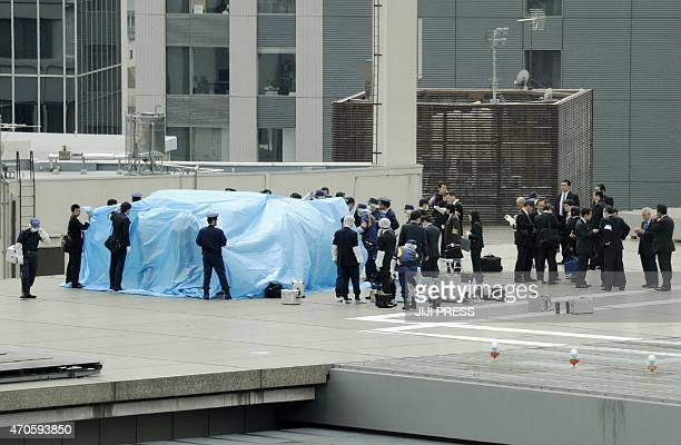 Japanese policemen cover with a blue sheet and inspect a small drone which was found on the roof of the Japanese prime minister's official residence...