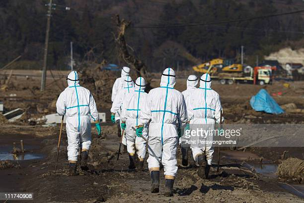 Japanese policemen in protective suites search for missing people within the exclusion zone about 20 kilometers away from Fukushima Nuclear Power...