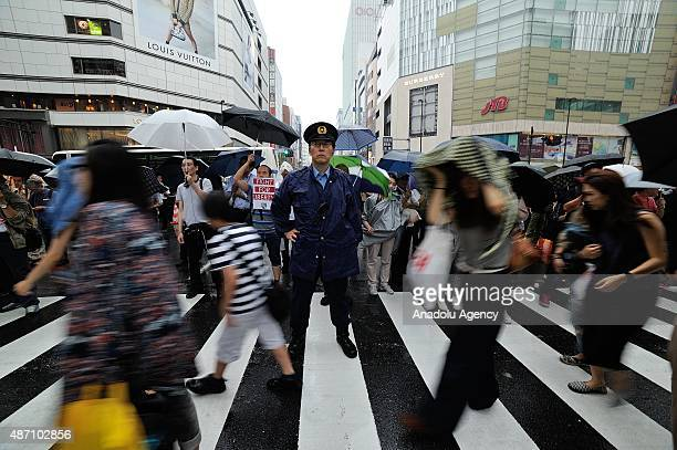 Japanese policemen stand guard as protesters attend an antigovernment rally in Tokyo on September 6 against Japan's Prime Minister Shinzo Abe's...
