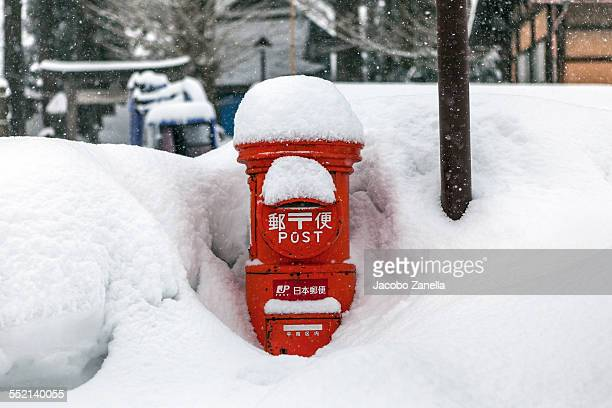 Japanese post box covered and surrounded by snow