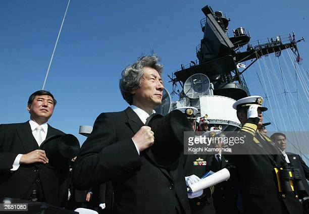 Japanese Premier Junichuro Koizumi and Defence Minister Shigeru Ishiba salute the Japanese Maritime SelfDefence Force during a naval review on...