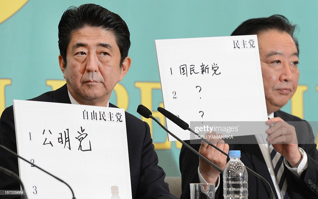 Japanese Prime Minister and Democratic Party of Japan leader Yoshihiko Noda (R) and former Prime Minister and Liberal Democratic Party President Shinzo Abe (L) show flips in which they write their closest party names during debates for the general election at the Japan National Press Club in Tokyo on November 30, 2012. Eleven leaders of Japanese political parties took part in the debates for the election on Decemver 16. AFP PHOTO/Toru YAMANAKA