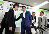 Japanese Prime Minister and ruling Liberal Demcratic Party President Shinzo Abe shakes hands with the LDP vice president Masahiko Komura at the LDP...