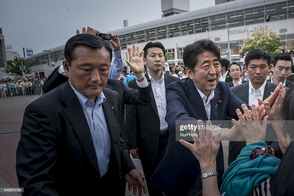 Japanese Prime Minister and ruling Liberal Democratic Party (LDP) president <a gi-track='captionPersonalityLinkClicked' href=/galleries/search?phrase=Shinzo+Abe&family=editorial&specificpeople=559017 ng-click='$event.stopPropagation()'>Shinzo Abe</a> shakes hands with his party supporters after he delivered a campaign speech for his partys candidate Nobuhiro Miura during the Upper House election campaign in Yokohama in Kanagawa prefecture, June 27, 2016 Japan.