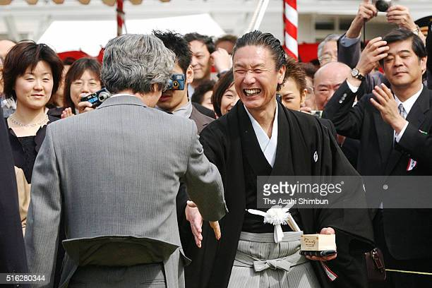 Japanese Prime Minister Junichiro Koizumi shakes hands with fashion designer Kansai Yamamoto during the cherry blossom viewing party at the Shinjuku...