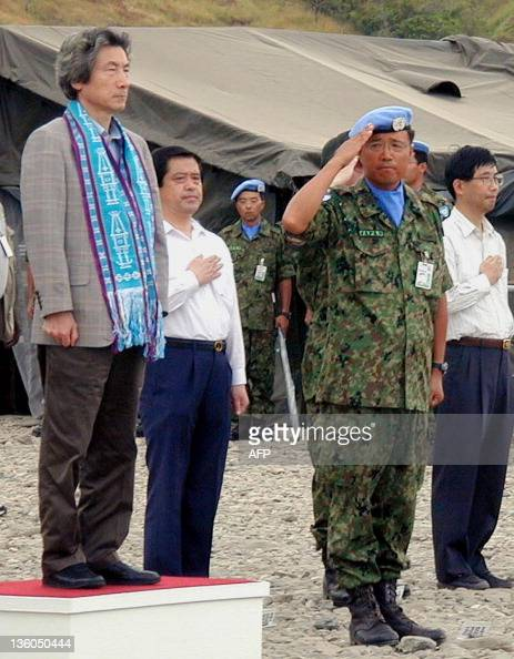 Japanese Prime Minister Junichiro Koizumi stands as one of the Japanese peacekeeping soldiers serving in East Timor salutes during the playing of...