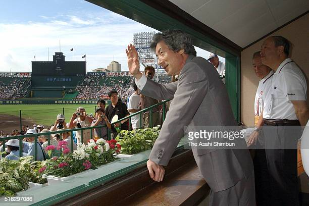 Japanese Prime Minister Junichiro Koizumi waves to fans on arrival to attend the opening ceremony of the Japanese High School Baseball Championship...
