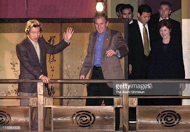 Japanese Prime Minister Junichiro Koizumi welcomes US President George W Bush and first lady Laura Bush at a Japanese restaurant on February 18 2002...