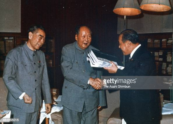 Japanese Prime Minister Kakuei Tanaka shakes hands with Chinese President Mao Zedong while Chinese Premier Zhou Enlai watches during Tanaka's visit...