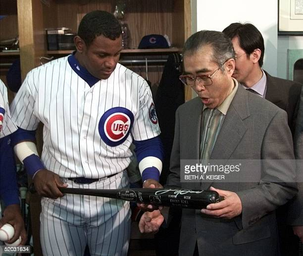 Japanese Prime Minister Keizo Obuchi reacts to a signed bat given to him by Chicago Cubs' Sammy Sosa in the Cubs' locker room before their game with...
