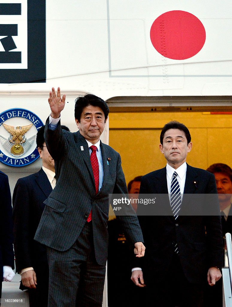 Japanese Prime Minister Shinzo Abe (L), accompanied by Foreign Minister Fumio Kishida (R) leaves Tokyo International Airport to travel to the US on February 21, 2013. Abe will have talks with US President Barack Obama for the first time since taking power. AFP PHOTO / JIJI PRESS JAPAN OUT