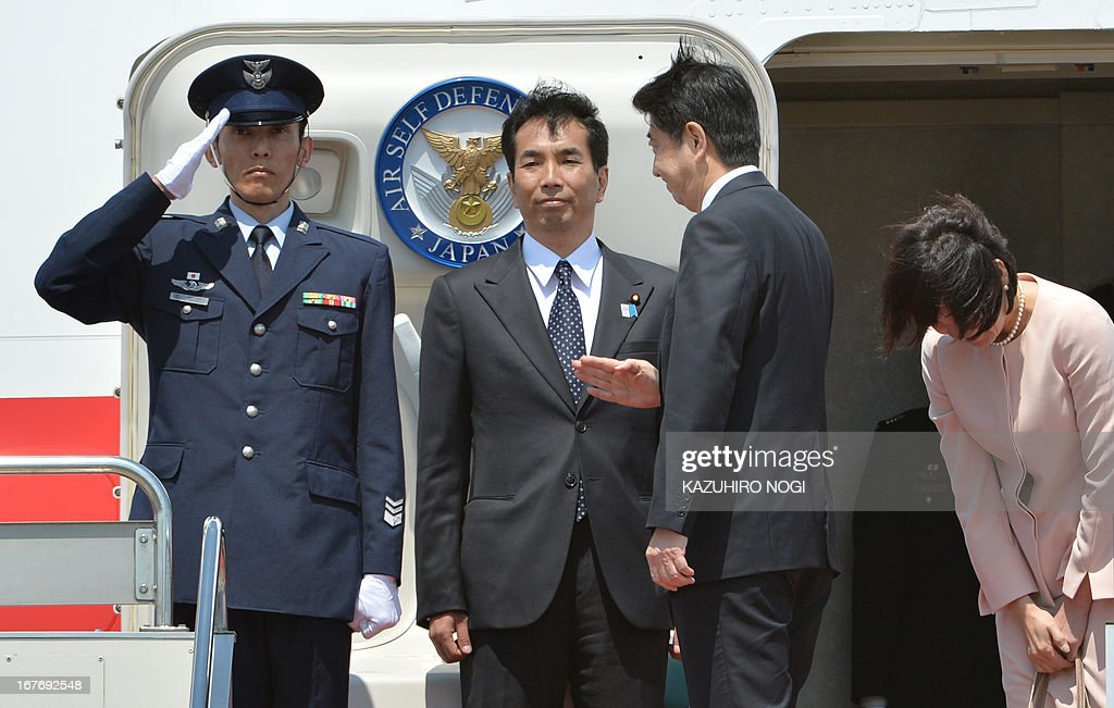 Japanese Prime Minister Shinzo Abe (2nd R), accompanied by his wife Akie (R), salutes a military officer upon his departure at Tokyo's Haneda airport on April 28, 2013. Abe left for Russia and he will also visit to Saudi Arabia, the United Arab Emirates and Turkey on a weeklong trip.