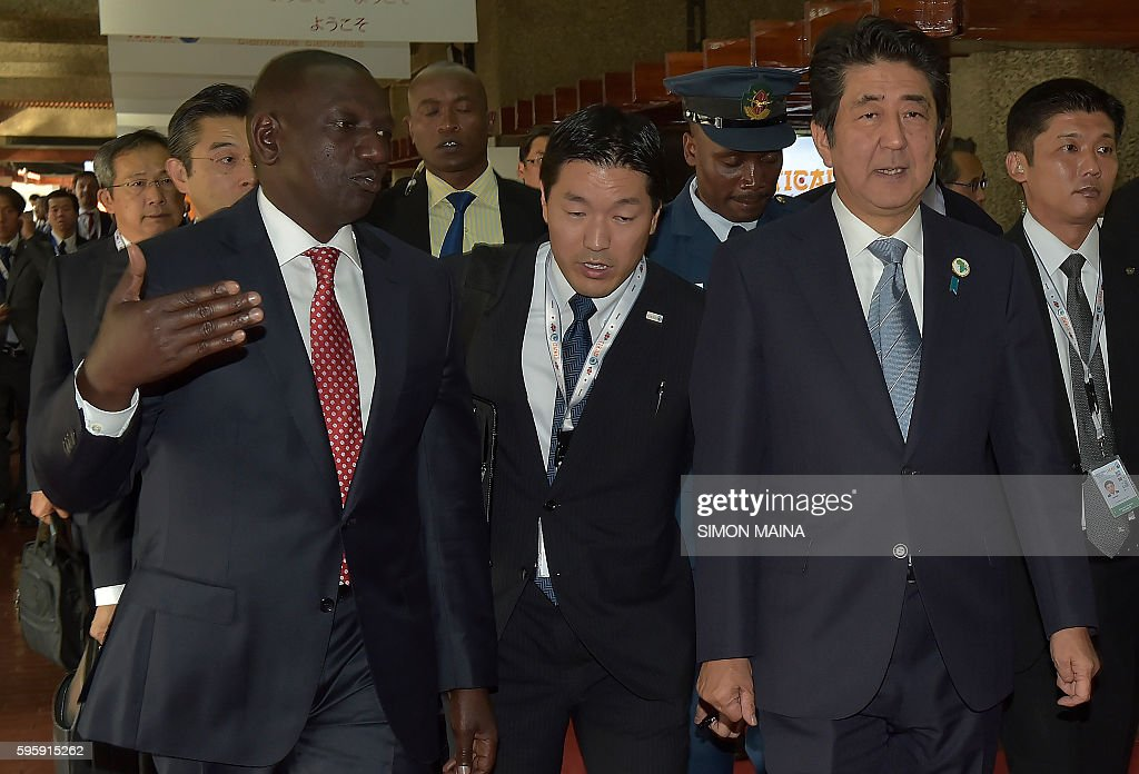 Japanese Prime Minister Shinzo Abe accompanied by kenya's Deputy President William Ruto arrives for a session with Kenya's Ministry of Health and...