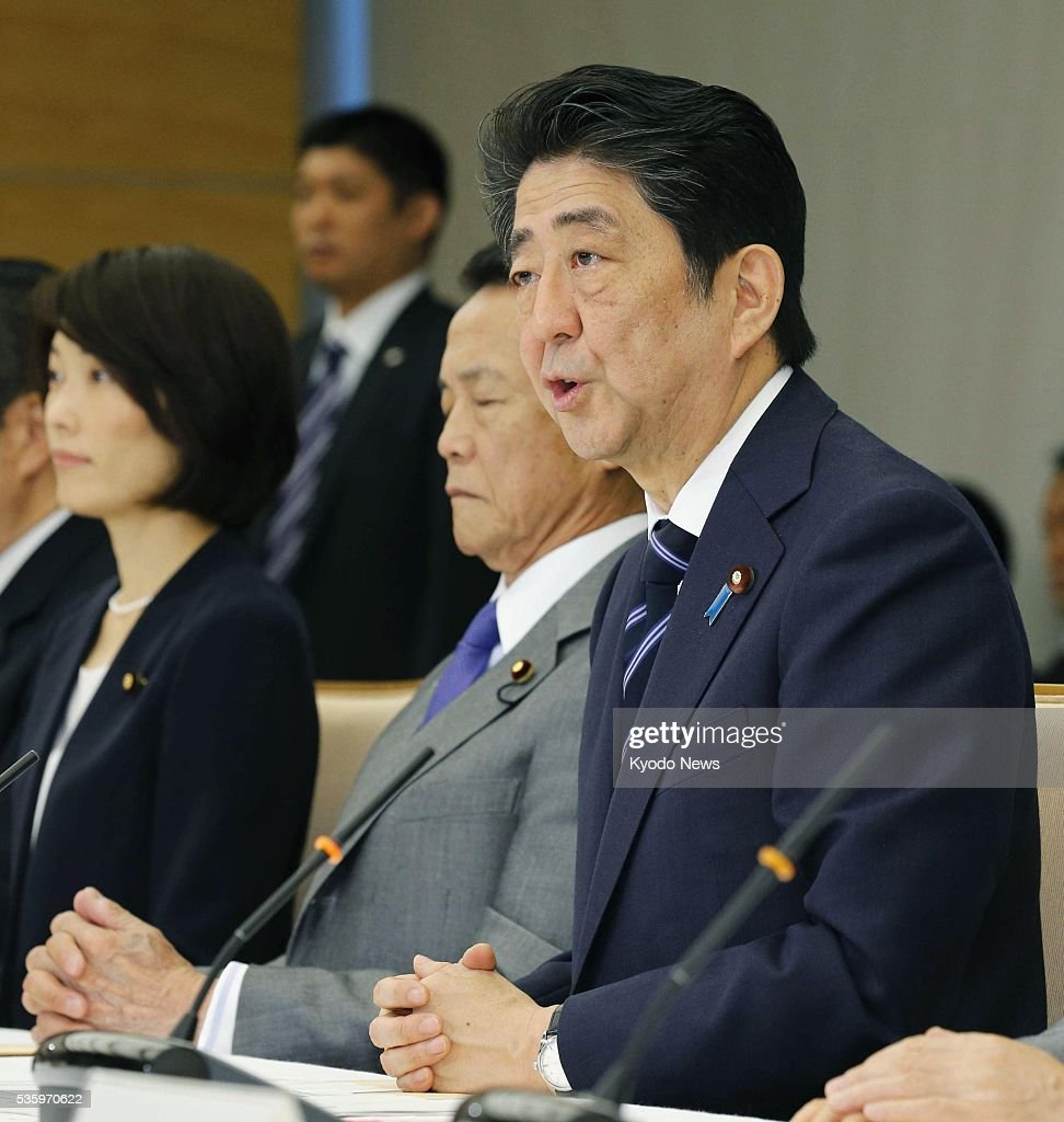 Japanese Prime Minister Shinzo Abe (far R) addresses a meeting of the government's taskforce on nuclear disaster at his office in Tokyo on May 31, 2016, as it agreed to lift the evacuation orders for three municipalities, issued in the wake of the 2011 Fukushima nuclear disaster. Abe pledged to provide strengthened support to the three.