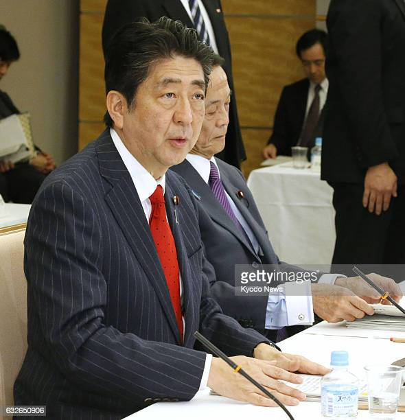 Japanese Prime Minister Shinzo Abe alongside Finance Minister Taro Aso speaks in a meeting of the Council on Economic and Fiscal Policy in Tokyo on...
