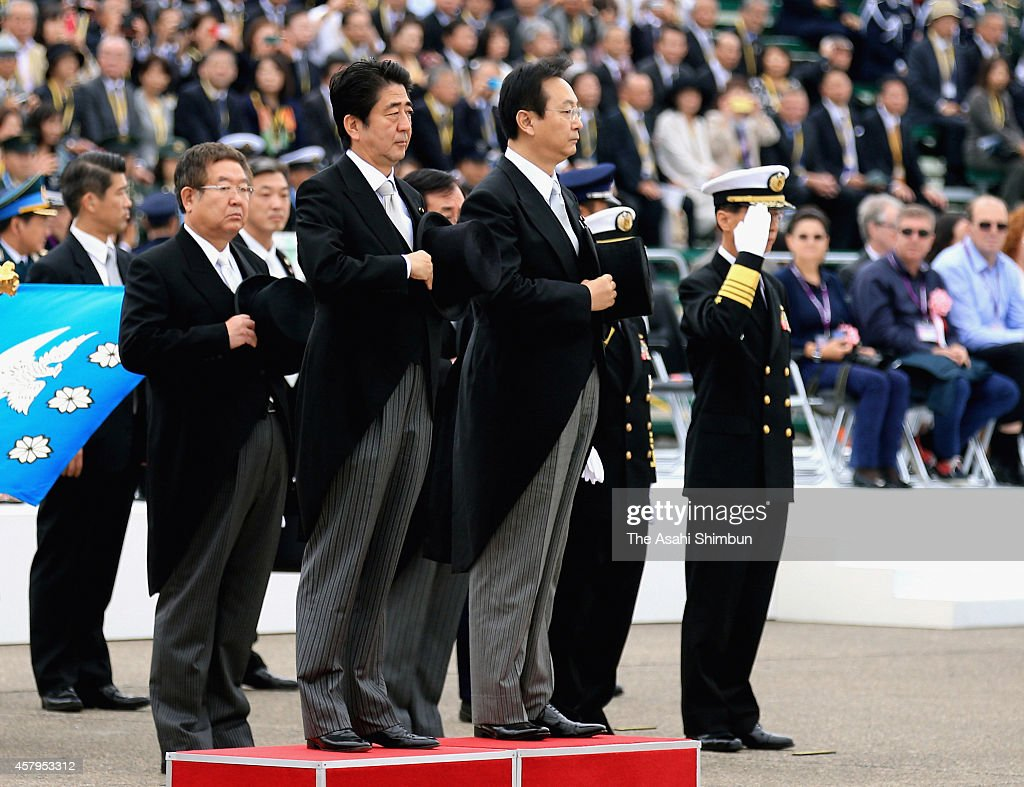 Japanese Prime Minister <a gi-track='captionPersonalityLinkClicked' href=/galleries/search?phrase=Shinzo+Abe&family=editorial&specificpeople=559017 ng-click='$event.stopPropagation()'>Shinzo Abe</a> (L) and Defense Minister <a gi-track='captionPersonalityLinkClicked' href=/galleries/search?phrase=Akinori+Eto&family=editorial&specificpeople=5129797 ng-click='$event.stopPropagation()'>Akinori Eto</a> (R) receive the honor guard during the air review at Japan Air Seld-Defense Force Hyakuri Air Base on October 26, 2014 in Omitama, Ibaraki, Japan. The air review is held to celebrate the 60th anniversary of foundation of the Japan's Seld-Defense Force.