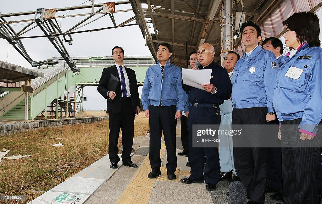 Japanese Prime Minister Shinzo Abe (2nd R) and Disaster Reconstruction Minister Takumi Nemoto (2nd L) listen to Tomioka Mayor Katsuya Endo (3rd L) during a visit to Tomioka Railway Station in Tomioka, Fukushima Prefecture, during a visit to the region on March 24, 2013. Tomioka residents were forced to evacuate from the town after the accident at the Fukushima Dai-ichi Nuclear Plant following the March, 2011 earthquake and tsunami disasters. JAPAN OUT AFP PHOTO/Jiji Press