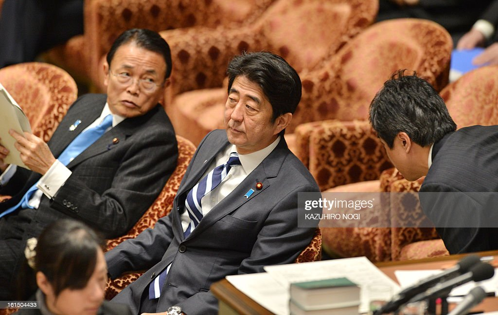 Japanese Prime Minister Shinzo Abe (C) and Finance Minister Taro Aso (L) attend a budget committee session of the lower house at parliament in Tokyo on February 12, 2013. AFP PHOTO / KAZUHIRO NOGI