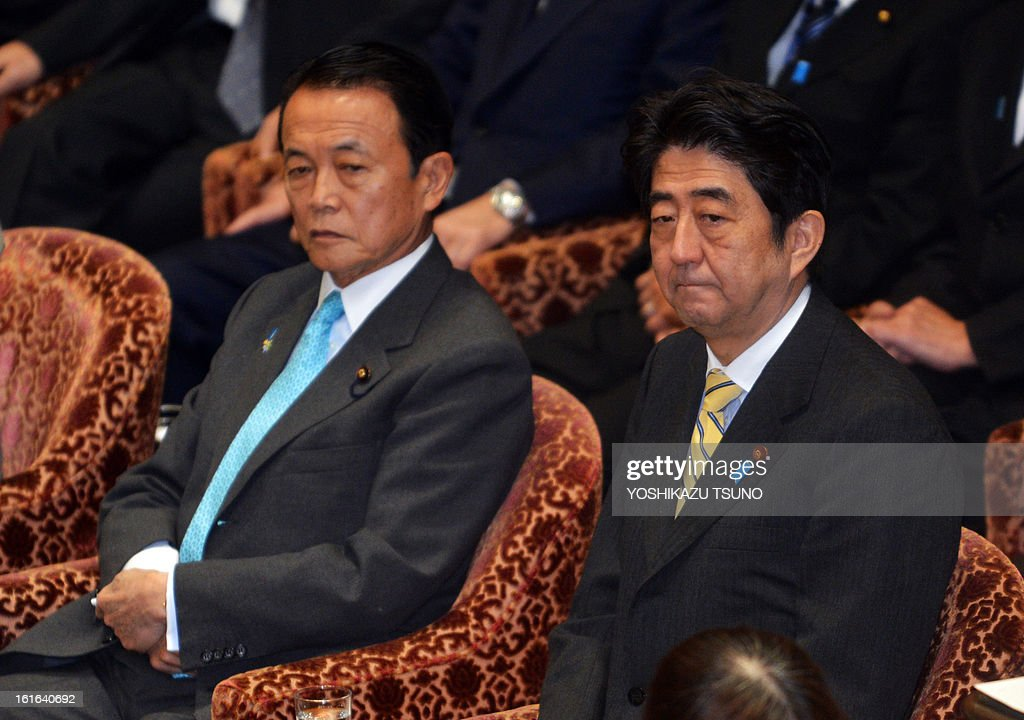 Japanese Prime Minister Shinzo Abe (R) and Finance Minister taro Aso (L) attend the Lower House's budget committee session at the National Diet in Tokyo on February 14, 2013. The governemnt and ruling coalition passed a 140 billion USD supplementary budget for the fiscal 2012 to finance economic stimulus. AFP PHOTO / Yoshikazu TSUNO