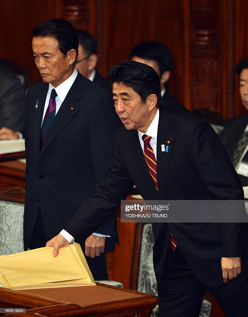 Japanese Prime Minister Shinzo Abe (R) and Finance Minister Taro Aso leave the Lower House's plenary session at the National Diet in Tokyo on February 28, 2013 after they delivered speeches. Faced with a territorial dispute with China, Abe quoted former British prime minister Margaret Thatcher stressing the rule of law over the 1982 Falklands war. AFP PHOTO / Yoshikazu TSUNO