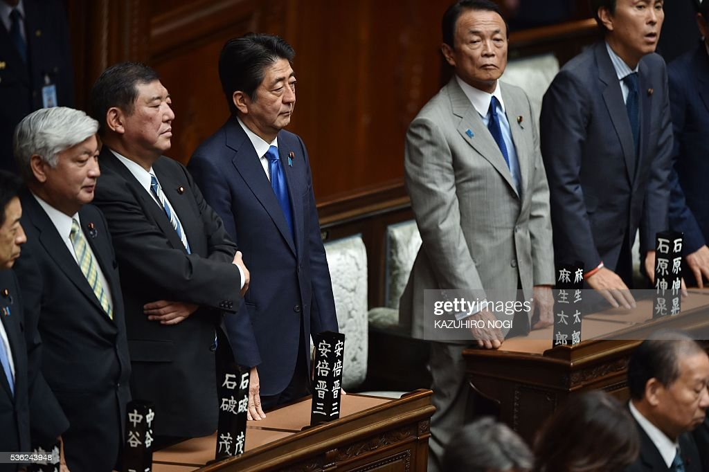 Japanese Prime Minister Shinzo Abe (C) and his cabinet members attend a plenary session of the House of Representatives at the end of 150-day regular Diet session on June 1, 2016. Japanese leader Shinzo Abe is set to announce June 1 that he will delay a consumption tax hike and launch another blast of government spending, underscoring his failure to ignite the limp economy, analysts said. / AFP / KAZUHIRO