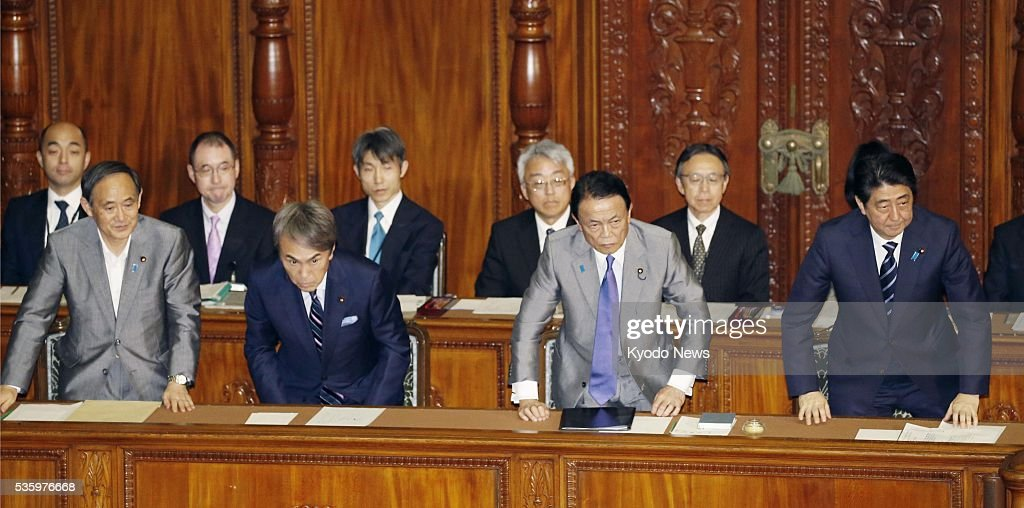 Japanese Prime Minister Shinzo Abe (R in front) and his Cabinet members bow after a motion of no-confidence against the Cabinet was voted down during a plenary session of the House of Representatives at the Diet in Tokyo on May 31, 2016.