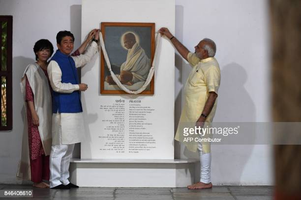 Japanese Prime Minister Shinzo Abe and his wife Akie Abe pay their respects to Mahatma Gandhi along with Indian Prime Minister Narendra Modi during...
