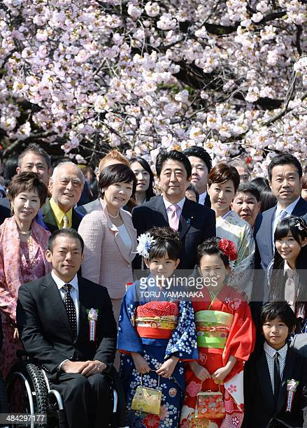 Japanese Prime Minister Shinzo Abe and his wife Akie pose for a group picture with invited guests during the cheery blossom viewing party in Tokyo on...