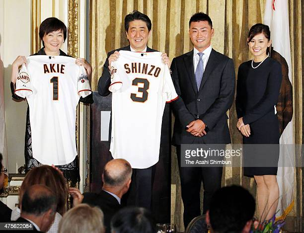 Japanese Prime Minister Shinzo Abe and his wife Akie show baseball shirts they were presented by Norichika Aoki of San Francisco Giants and his wife...