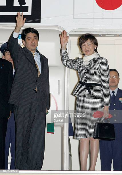 Japanese Prime Minister Shinzo Abe and his wife Akie wave as they visit the Philippines at Tokyo International Airport on December 8 2006 in Tokyo...