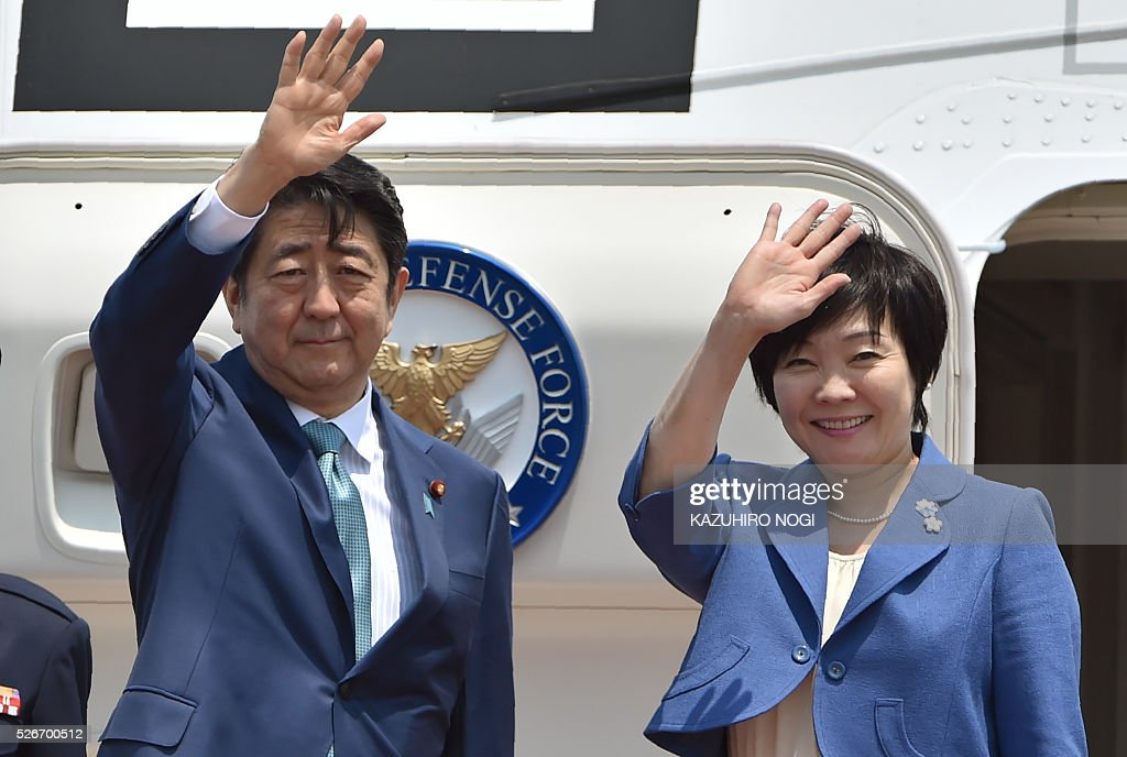 Japanese Prime Minister Shinzo Abe (L) and his wife Akie (R) wave as they depart for major European countries at Tokyo's Haneda airport on May 1, 2016. Abe will visit Italy, France, Belgium, Germany, Britain, and Russia during his week-long diplomatic trip. / AFP / KAZUHIRO