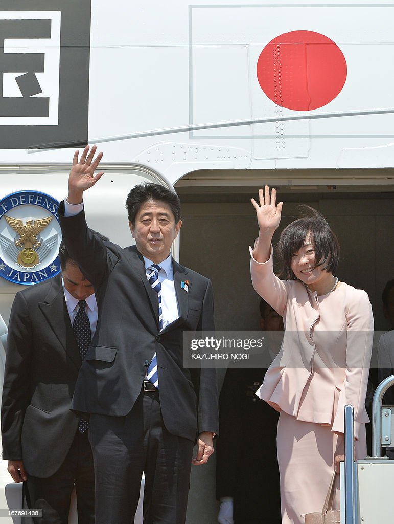 Japanese Prime Minister Shinzo Abe (C) and his wife Akie (R) wave to well-wishers upon his departure at Tokyo's Haneda airport on April 28, 2013. Abe left for Russia and he will also visit to Saudi Arabia, the United Arab Emirates and Turkey on a weeklong trip.
